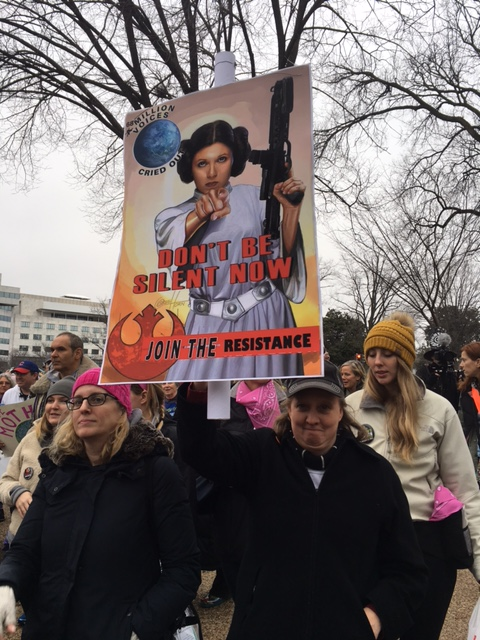 "A woman carrying a sign featuring Princess Leia from ""Star Wars"" walks with the crowd headed toward the Women's March on Washington on Saturday, Jan. 21, 2017. (WTOP/Jenny Glick)"