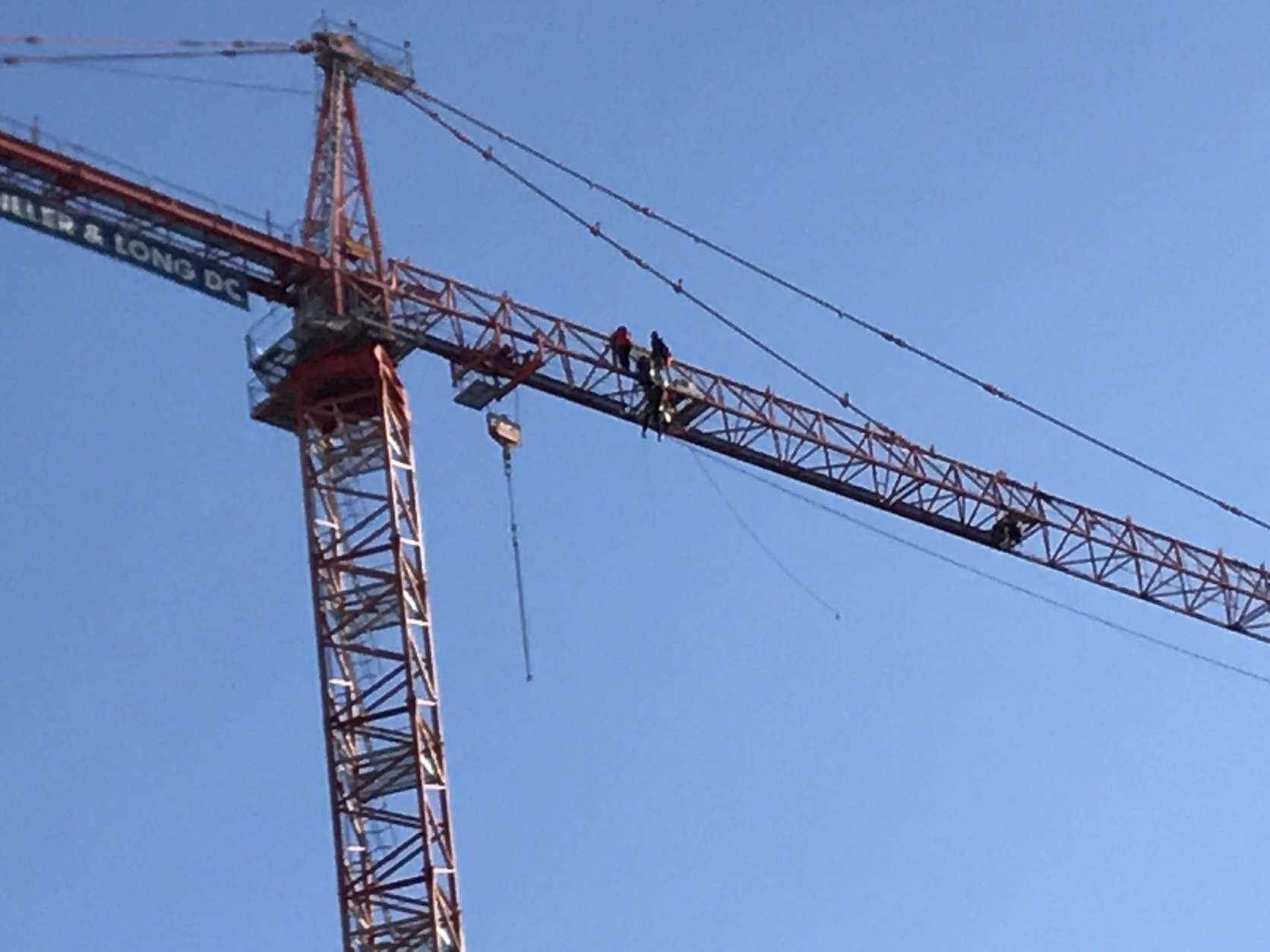 """Protesters sit in a crane in downtown D.C. Wednesday morning. Greenpeace says seven of their activists are hanging a """"Resist"""" banner above the White House. (WTOP/Neal Augenstein)"""