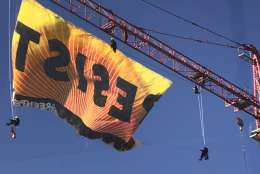 """Protesters from Greenpeace unfurl a banner reading """"Resist"""" from a construction crane in downtown D.C. Wednesday morning. (WTOP/Neal Augenstein)"""
