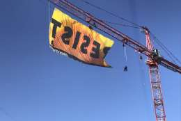 """Protesters from Greenpeace unfurl a banner reading """"Resist"""" on a construction crane in downtown D.C. Wednesday morning. (WTOP/Neal Augenstein)"""