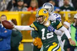 GREEN BAY, WI - DECEMBER 13:  Quarterback  Aaron Rodgers #12 of the Green Bay Packers is tackled by  Brandon Carr #39 of the Dallas Cowboys in the first half at Lambeau Field on December 13, 2015 in Green Bay, Wisconsin. The Green Bay Packers defeated the Dallas Cowboys 28 to 7.  (Photo by Joe Robbins/Getty Images)