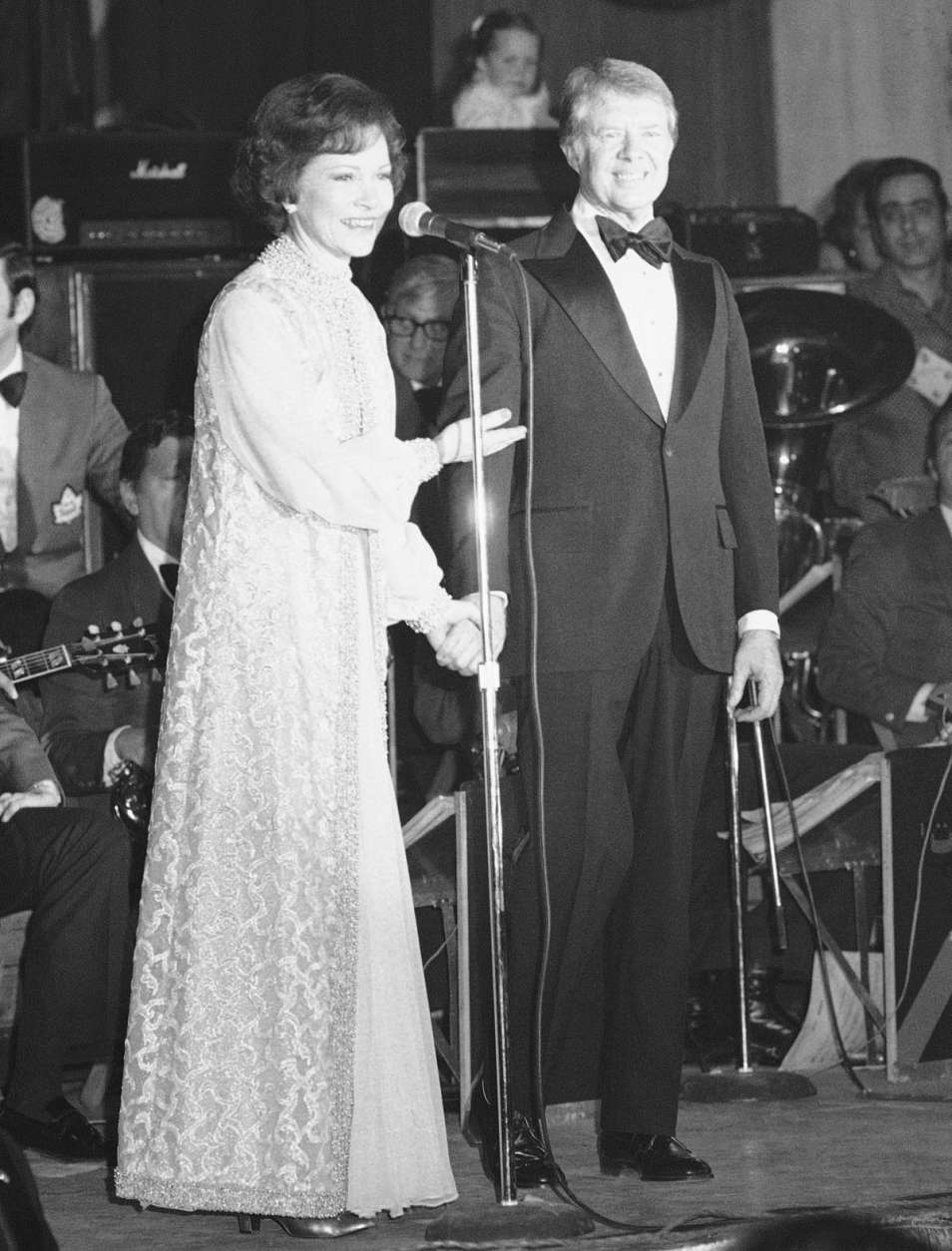 President Jimmy Carter holds his wife Rosalynn's hand as she says a few words at an inaugural party in Washington on Thursday, Jan. 21, 1977. The Carters attended seven parties at four hotels, the railroad station, a government building and an armory. (AP Photo)