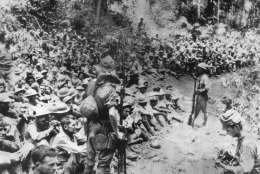 "Japanese soldiers stand guard over American war prisoners just before the start of the ""March of Death"" for the soldiers of Bataan and Corregidor in 1942.  This photograph was stolen from the Japanese by the Philippines during Japan's three-year occupation in World War II.  (AP Photo/U.S. Marine Corps)"