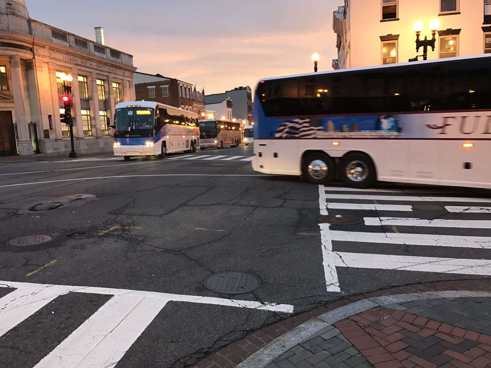 Escorted buses snake through Georgetown to get to downtown D.C. for the inauguration. (WTOP/Neal Augenstein)
