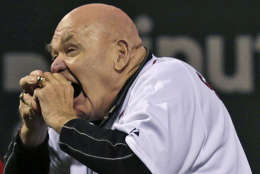 """Former professional wrestler George """"The Animal"""" Steele bites the baseball before throwing out the ceremonial first pitch prior to a baseball game against the Baltimore Orioles at Fenway Park in Boston, Friday, Sept. 21, 2012. (AP Photo/Charles Krupa)"""
