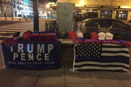A New Yorker headed to New York University sells Trump merchandise near the White House early Friday morning. (WTOP/Dennis Foley)