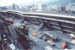 COLLAPSED HIGHWAY: Police and firemen survey the extensive damage to the collapsed Kobe-Osaka highway in Eastern Kobe, Wednesday, January 18, 1995. The elevated highway collapsed when a major 7.2 magnitude earthquake hit this Western Japan port city Tuesday morning. More than 4,000 were killed in the disaster. (AP-Photo/stf/Atsushi Tsukada/-01/18/1995-)