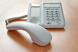 Telephone on an window lit office desk with the receiver off the hook and the call on hold