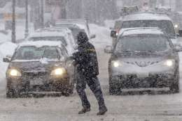 A pedestrian crosses the street in front of vehicles during a snowstorm, Sunday, Feb. 12, 2017, in Waltham, Mass. (AP Photo/Steven Senne)