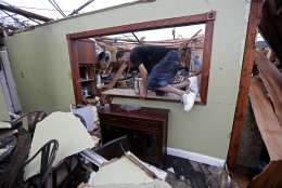 Gregory Rugon climbs out of his home after failing to find his glasses that he lost taking cover after a tornado hit his Warren Drive home, in the New Orleans East section of New Orleans, Tuesday, Feb. 7, 2017. (AP Photo/Gerald Herbert)