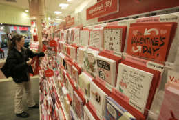 """Anti-Valentine Day cards rest on the shelf as Lori Schwartz picks out Valentines Day cards for her children, Wednesday, Feb. 7, 2007, in Beachwood, Ohio. Sensing a growing trend, and more potential customers, Cleveland-based American Greetings Corp. has launched a new line of """"anti-Valentine's"""" cards, expressions for lovers who'd rather be big goofs than big flirts, as well as singles not struck by Cupid's arrow this time of year. (AP Photo/Tony Dejak)"""