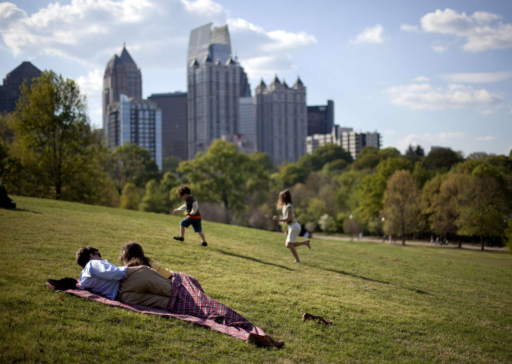 A couple enjoy a sunny afternoon against the backdrop of the Midtown skyline from Piedmont Park in Atlanta, Sunday, March 25, 2012. (AP Photo/David Goldman)