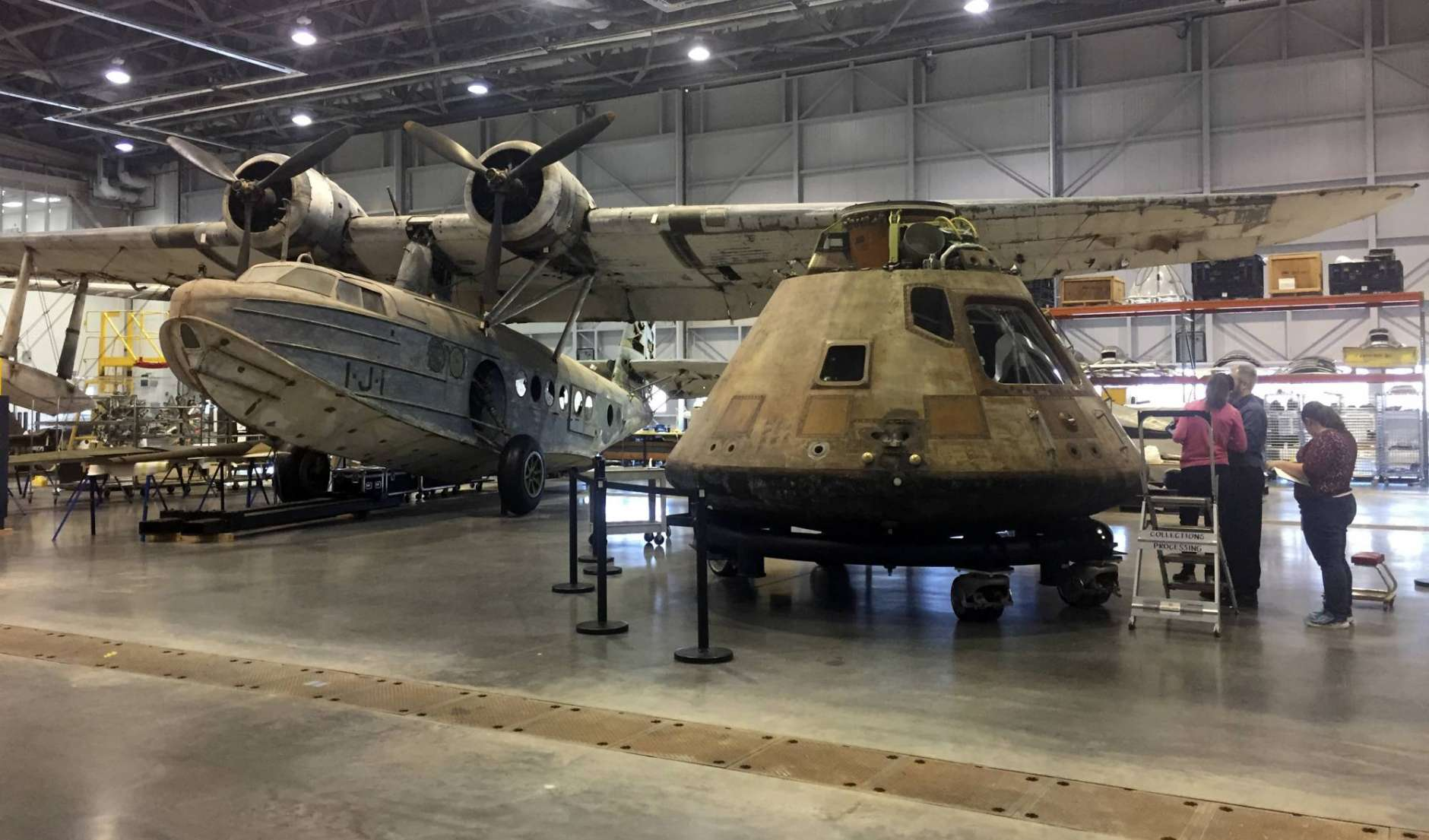 In this photo taken Feb. 17, 2017, the Apollo 11 capsule sits in the restoration hanger at the National Air and Space Museum's Steven F. Udvar-Hazy Center in Chantilly, Va., ahead of a planned four-city tour. The Apollo 11 command module, which travelled more than 950,000 miles to take Americans to the moon and back in 1969, is going on a road trip, leaving the Smithsonian for the first time in more than four decades. The airplane at left is the only aircraft in the Smithsonian's collection that was stationed at Pearl Harbor on Dec. 7, 1941, the day the naval base at the harbor was attacked by Japan. (AP Photo/Jessica Gresko)