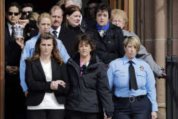 Sharon Guindon, bottom center, mother of slain Prince William County, Va., Police Officer Ashley Guindon, leads mourners out of Sacred Heart Church after her funeral, Monday, March 7, 2016, in Springfield, Mass. Guindon, 28, a Springfield native, was killed during her first shift on the job Feb. 27, 2016 while responding to a domestic dispute in Woodbridge, Va. On the one year anniversary of Ashley's death, Sharon Guindon released a letter thanking scores of people and businesses who helped her family in the chaotic hours and days after the shooting. (AP Photo/Elise Amendola)