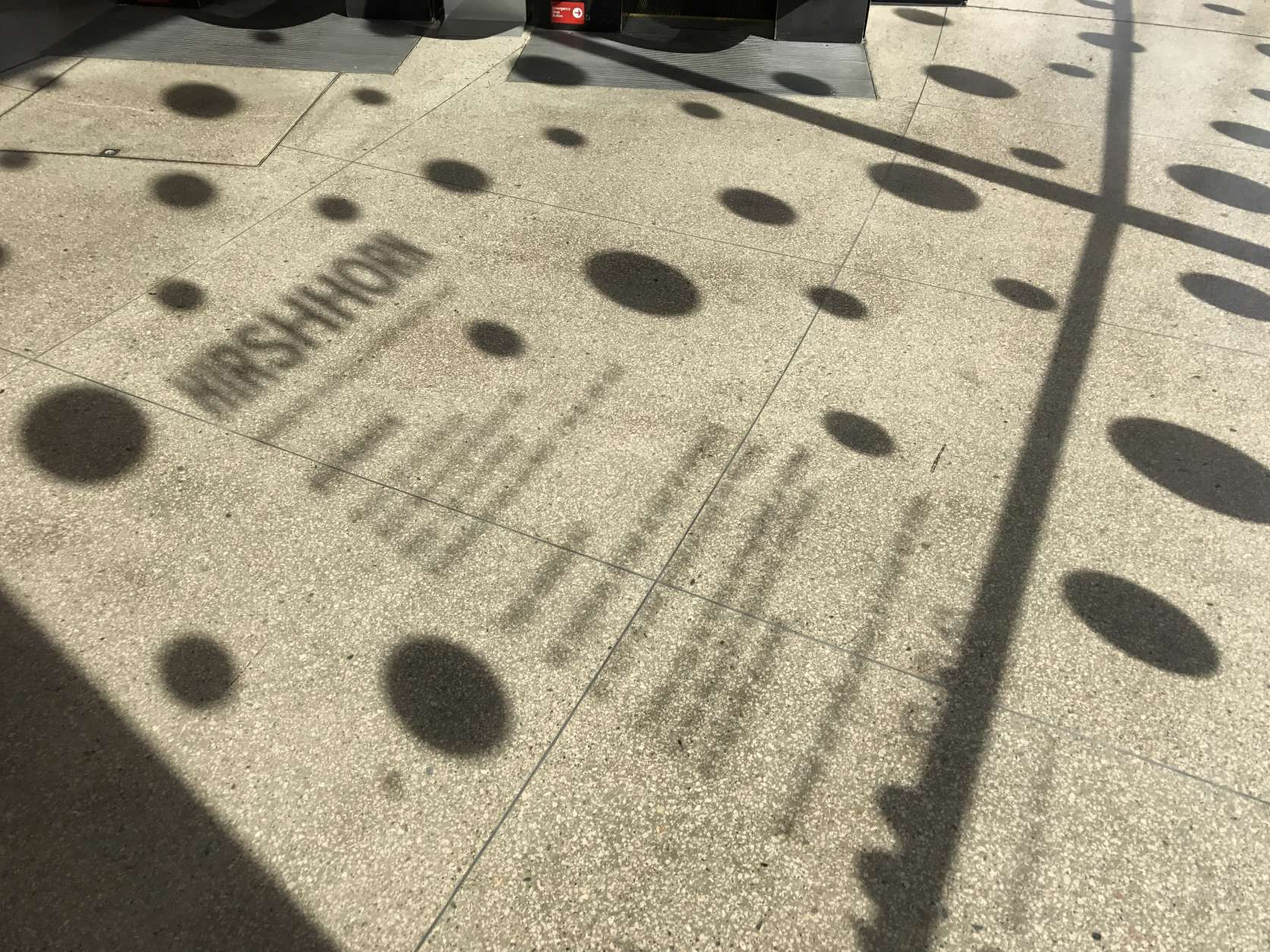 A reflection of the Hirshorn Collection's front door in the afternoon sun. (WTOP/Megan Cloherty)