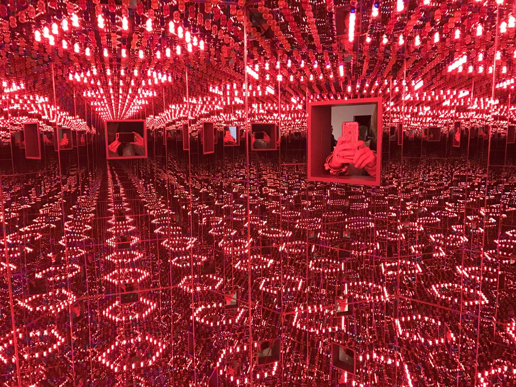 There are two windows into the octagonal Love Forever mirrored room so visitors can interact with each other inside. (WTOP/Megan Cloherty)