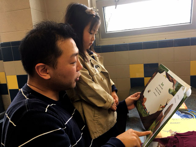 Moses Song and his daughter, Catherine Song, read a book together at Robert E. Lee High School in Springfield, Virginia on Saturday, Feb. 25. (WTOP/JennyGlick)