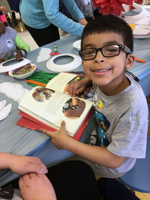 Seven-year-old David Perez reads one of the books he picked out of the 20,000 books to choose from at the giveaway. (WTOP/Jenny Glick)