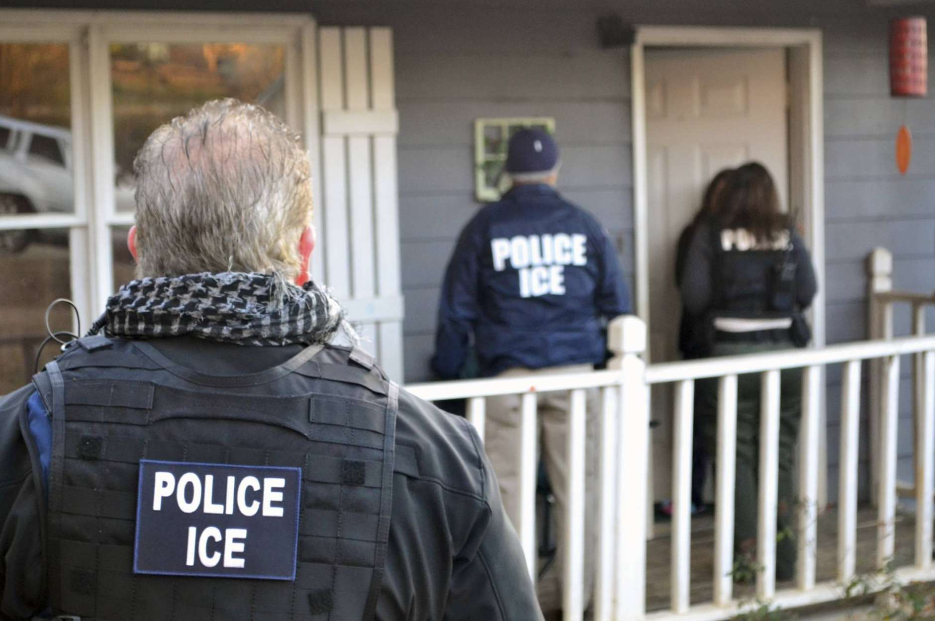 FILE — In this Feb. 9, 2017, photo provided U.S. Immigration and Customs Enforcement, ICE agents at a home in Atlanta, during a targeted enforcement operation aimed at immigration fugitives, re-entrants and at-large criminal aliens. (Bryan Cox/ICE via AP)