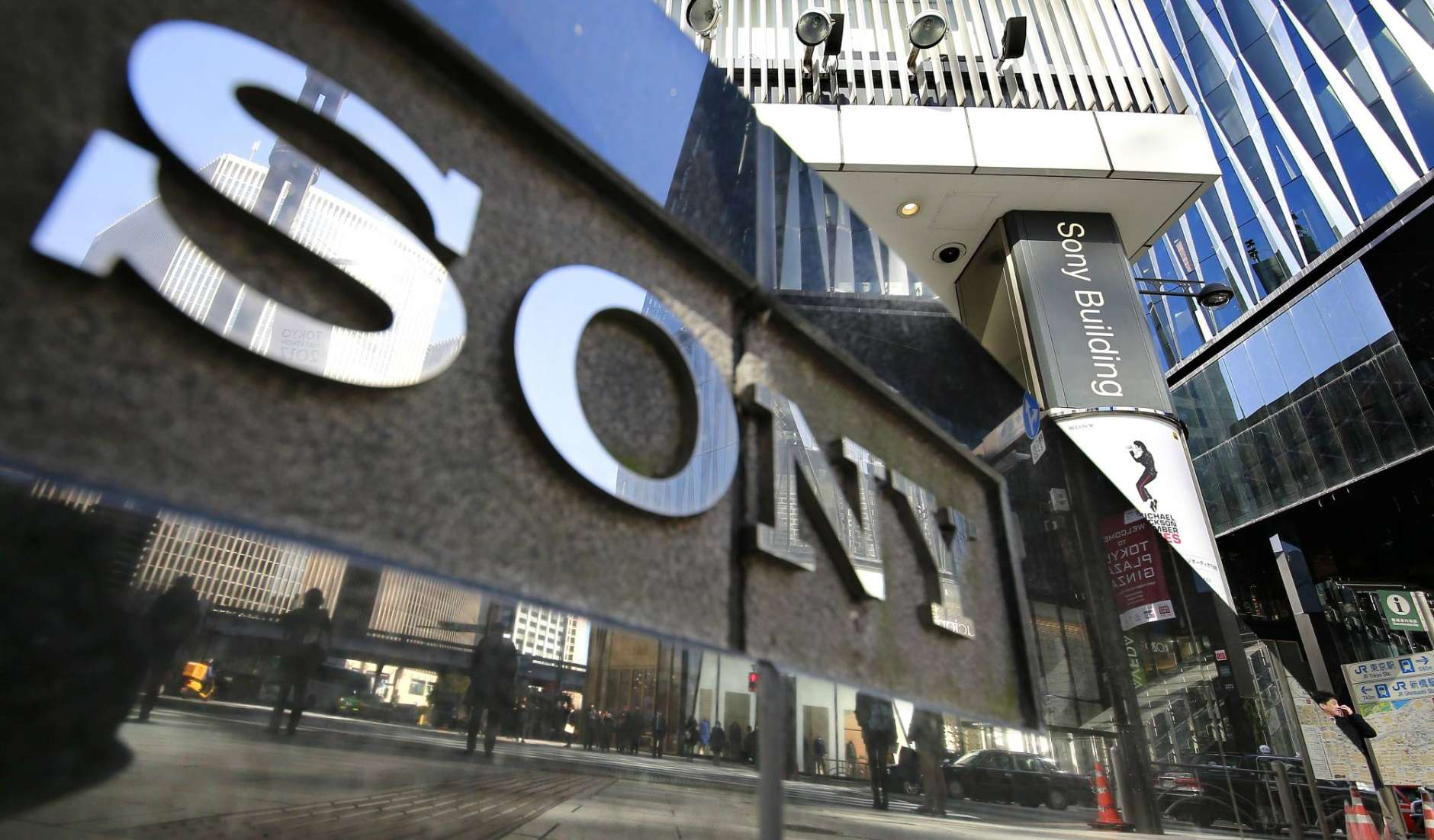 People are reflected on a wall of the Sony showroom building at Ginza shopping district in Tokyo, Thursday, Feb. 2, 2017.  Japanese electronics and entertainment company Sony Corp. said its profit dropped 84 percent in October-December as losses in its movie division offset healthy results in its video game business. (AP Photo/Shizuo Kambayashi)