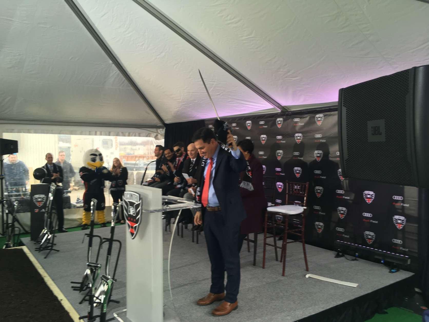 D.C. United Managing General Partner Jason Levien holds up a machete at the Audi Field groundbreaking. (WTOP/Noah Frank)