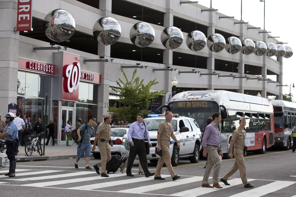 Staff of the Naval Sea Systems Command headquarters walk away from Nationals Park after being bused there from the Washington Navy Yard. (AP Photo/Jacquelyn Martin)