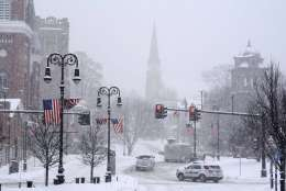 Vehicles navigate the intersection at Monument Square, Sunday, Feb. 12, 2017, in North Adams, Mass., during a winter storm which brought blizzard conditions and heavy snow to the region. North Adams Mayor Richard Alcombright called for a snow emergency from 9 a.m. on Sunday until Monday, at 11 p.m. (Gillian Jones/The Berkshire Eagle via AP)