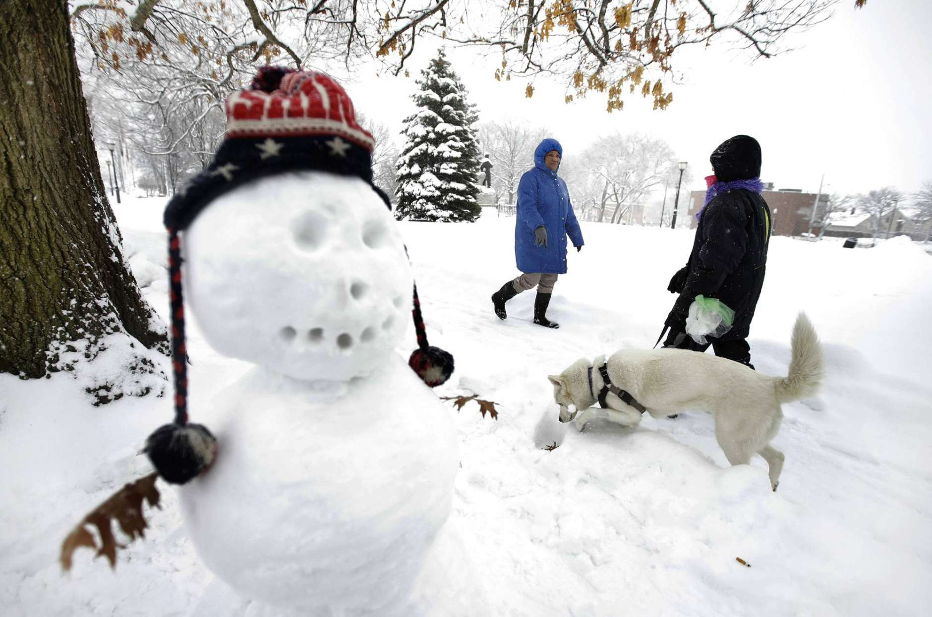 Tina Fuller, 60, of Waltham, Mass., behind center, walks past a snowman and a person walking a dog, Sunday, Feb. 12, 2017, in Waltham, Mass. Officials in the Northeast are urging people take precautions and schools have begun announcing cancellations as another winter blast of snow moved into the region. (AP Photo/Steven Senne)