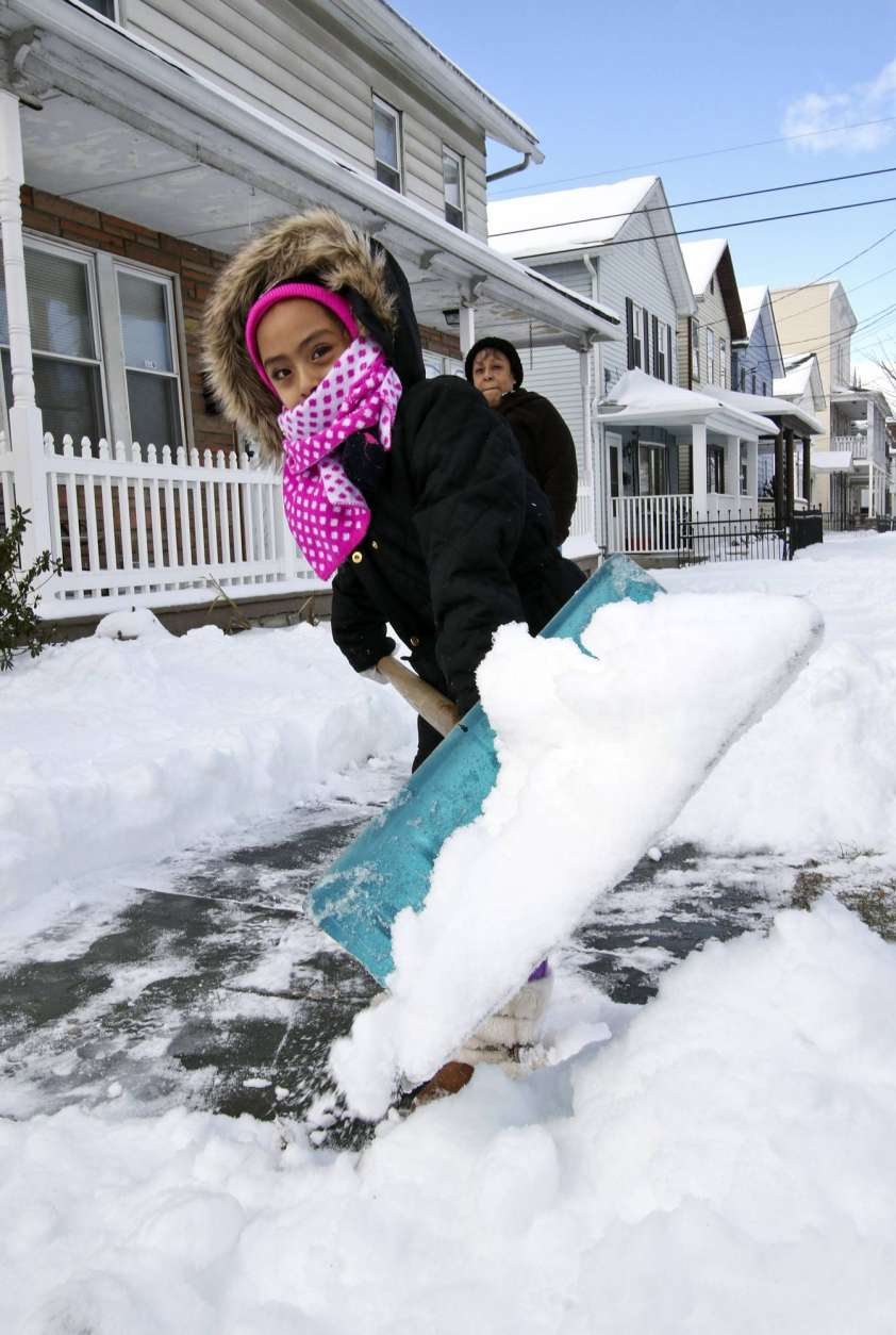 Six-year-old Ariana Ocampos helps shovel a sidewalk on River Street in Scranton, Pa., Thursday Feb. 9, 2017 after an overnight stormed dropped about 7 inches of snow. (Michael J. Mullen/The Times & Tribune via AP)