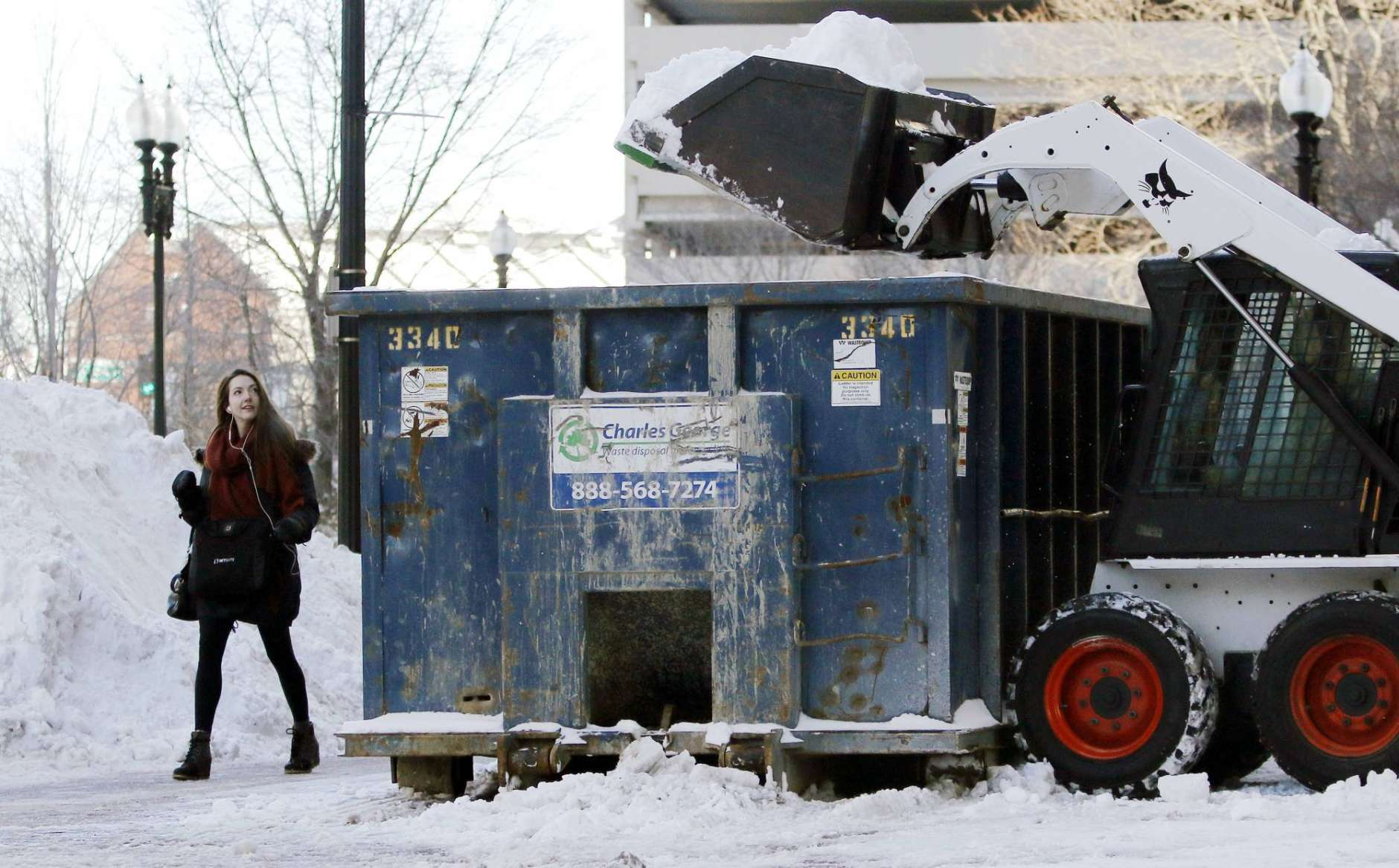 A pedestrian walks past a snow clearing operation, Friday, Feb. 10, 2017, in Boston after the previous day's snowstorm. (AP Photo/Bill Sikes)