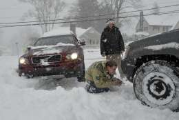 Nick Sinon looks for a place to attach his tow-strap to the front of his four wheel drive Jeep as he and Brian Brady try to help a stranded motorist get out of a snowbank in Bristol, Conn., Thursday afternoon, Feb. 9, 2017. Connecticut Gov. Dannel P. Malloy is urging people to stay off the roads while crews clean up at the end of a storm that dumped up to 18 inches of snow in parts of the state. (John Woike/Hartford Courant via AP)