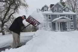"""Larry Habermehl shovels his driveway on King Street in Enfield, Conn., Thursday, Feb. 9, 2017. Habermehl said, """"I need the exercise and I don't like plows gouging up my lawn."""" (Brad Horrigan/Hartford Courant via AP)"""