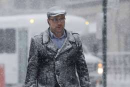 A man covered in snow walks toward the PATH train station terminal, Thursday, Feb. 9, 2017, in Hoboken, N.J. A powerful, fast-moving storm swept through the northeastern U.S. Thursday, making for a slippery morning commute and leaving some residents bracing for blizzard conditions. (AP Photo/Julio Cortez)