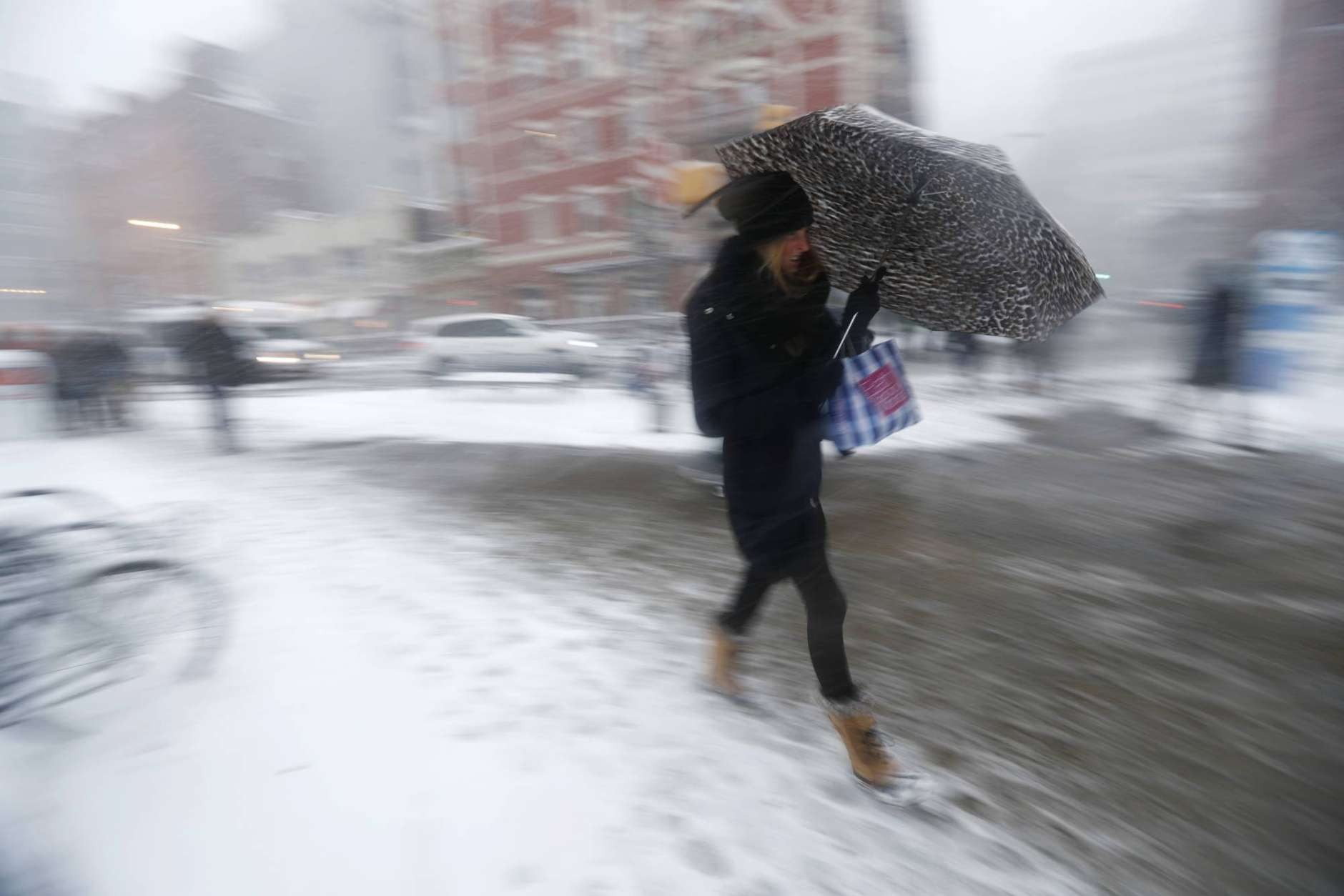 A woman uses an umbrella to shield herself from falling snow while approaching the Hoboken PATH train terminal, Thursday, Feb. 9, 2017, in Hoboken, N.J. A powerful, fast-moving storm swept through the northeastern U.S. Thursday, making for a slippery morning commute and leaving some residents bracing for blizzard conditions. (AP Photo/Julio Cortez)