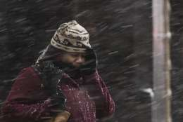 A woman shields her face during a winter storm in Philadelphia, Thursday, Feb. 9, 2017. A powerful, fast-moving storm swept through the northeastern U.S. Thursday, making for a slippery morning commute and leaving some residents bracing for blizzard conditions. (AP Photo/Matt Rourke)