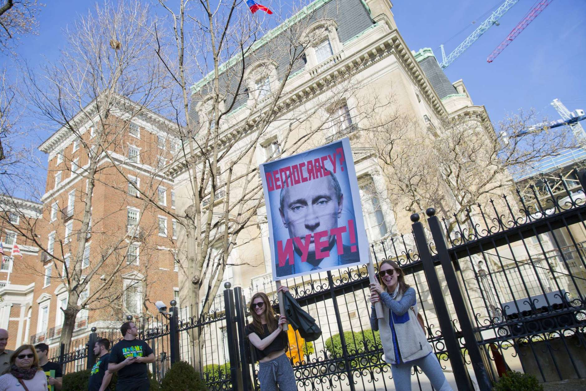 A pair of demonstrators hold up a sign showing Russian President Vladimir Putin in front of the Russian Ambassador's Residence in downtown Washington during a march toward the White House during a 'Not My President's Day' rally, Monday, Feb. 20, 2017.  Anti-Trump activists seized on Monday's federal holiday to organize rallies in cities around the country to oppose policies for President Donald Trump. (AP Photo/Pablo Martinez Monsivais)
