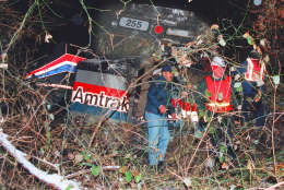 Investigators look over the front engine of the Amtrak train that collided with a MARC commuter train during a snow storm Friday, Feb. 16, 1996 in Silver Spring, Md. At least 12 people were killed and a score were injured. (AP Photo/Ruth Fremson)