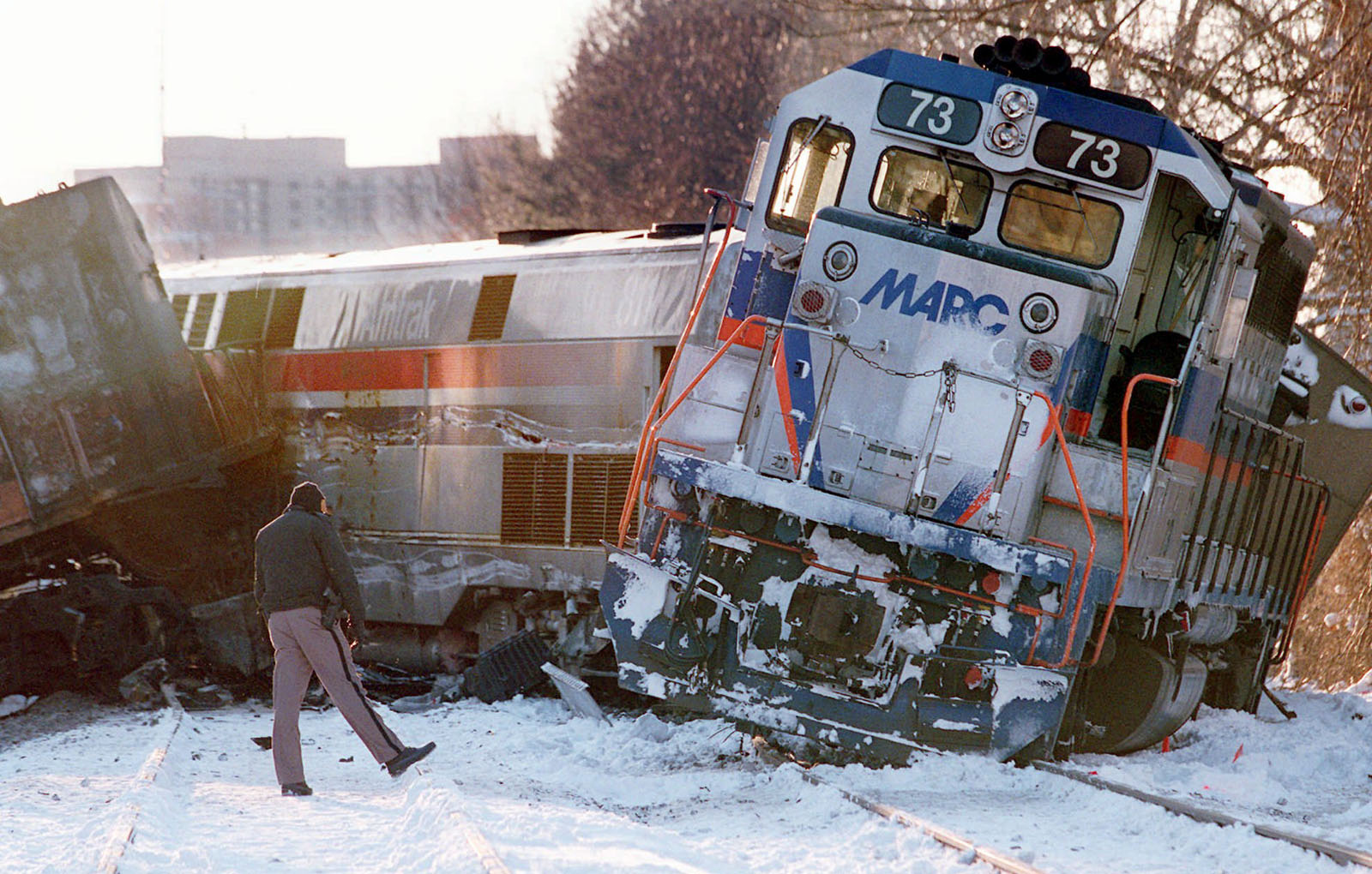 A police officer looks at the  site of a train crash  in Silver Spring, Md. Saturday Feb. 17, 1996. A Marc commuter train, right, carrying Job Corps youths home on a snowy evening Friday was crushed by an Amtrak train bound for Chicago, leaving at least 11 passengers dead. Transit officials said there were only 17 passengers on the commuter train, and Job Corps officials said 14 trainees from a West Virginia center had been aboard, returning to the Washington, D.C., area for the weekend. (AP Photo/Ruth Fremson)
