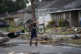 A man with a bicycle walks past debris from destroyed homes after a tornado tore through the eastern neighborhood in New Orleans, Tuesday, Feb. 7, 2017. Gov. John Bel Edwards has declared a state of emergency for Louisiana after a severe storm moved across the state's southeast corner, including the parishes of Ascension, Livingston, Orleans, St. James, St. Tammany and Tangipahoa. (AP Photo/Gerald Herbert)