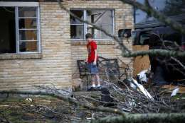 A boy holds his dog after a tornado tore through the New Orleans East neighborhood in New Orleans, Tuesday, Feb. 7, 2017. (AP Photo/Gerald Herbert)