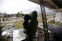 Eshon Trosclair holds her son Camron Chapital after a tornado tore through home while they were inside Tuesday, Feb. 7, 2017 in the eastern part of New Orleans.  The National Weather Service says at least three confirmed tornadoes have touched down, including one inside the New Orleans city limits. Buildings have been damaged and power lines are down. (AP Photo/Gerald Herbert)