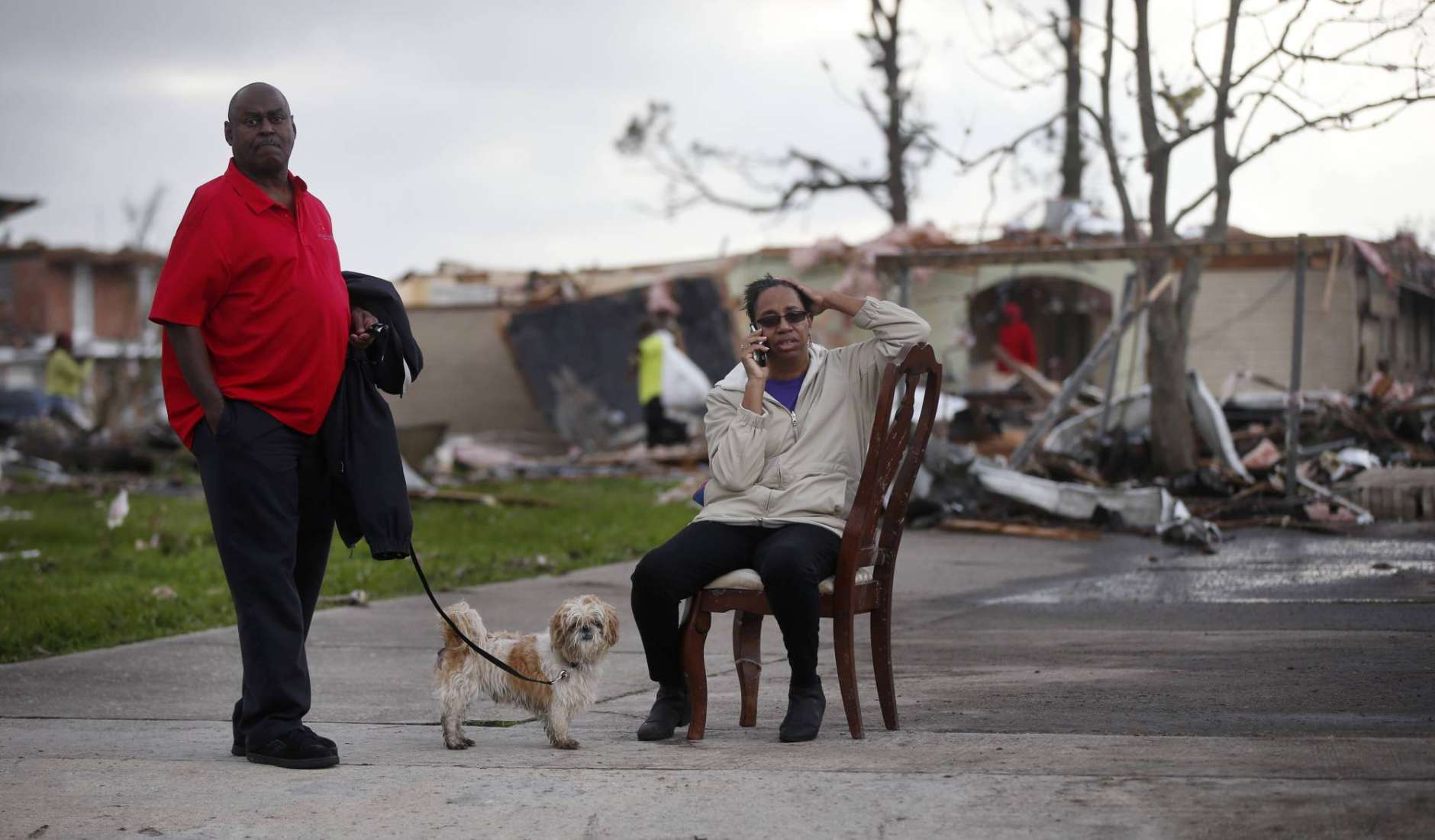 """Claire White sits in a chair and talks on the phone next to her husband Roy White and dog """"JD"""" across the street from their destroyed home after a tornado tore through the eastern neighborhood in New Orleans, Tuesday, Feb. 7, 2017. Gov. John Bel Edwards has declared a state of emergency for Louisiana after a severe storm moved across the state's southeast corner, including the parishes of Ascension, Livingston, Orleans, St. James, St. Tammany and Tangipahoa. (AP Photo/Gerald Herbert)"""