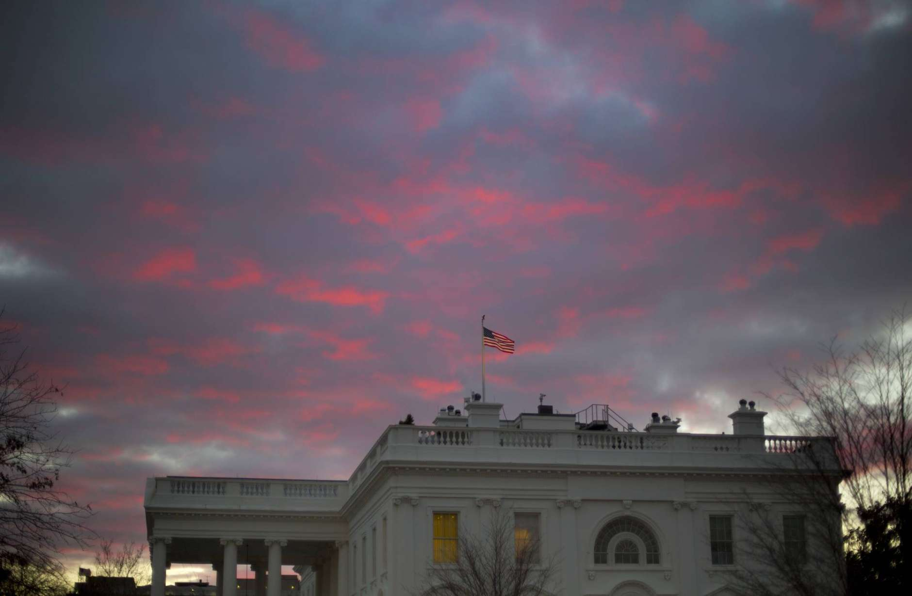 FILE - In this Jan. 27, 2017, file photo, day breaks over the White House in Washington. Two weeks into his presidency, Donald Trump has thrown Washington into a state of anxious uncertainty. Policy pronouncements sprout up from the White House in rapid succession. Some have far-reaching implications, most notably Trump's temporary refugee and immigration ban, but others disappear without explanation, including planned executive actions on cybersecurity and the president's demand for an investigation into unsubstantiated voter fraud. The day's agenda can quickly be overtaken by presidential tweets, which often start flashing on smartphones just as the nation's capital is waking up. (AP Photo/Pablo Martinez Monsivais, File)