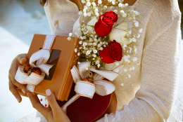 Close up shot of female hands holding gifts wrapped with white ribbon and bouquet of red roses. Time for gifts. Shallow depth of field with focus on gifts.Outdoors shot, Horizontal