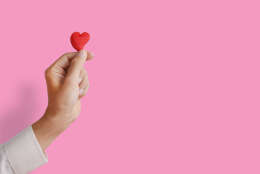 Man's hand holding and showing heart shape, love concept, give love, or valentine's day season. Pink background.