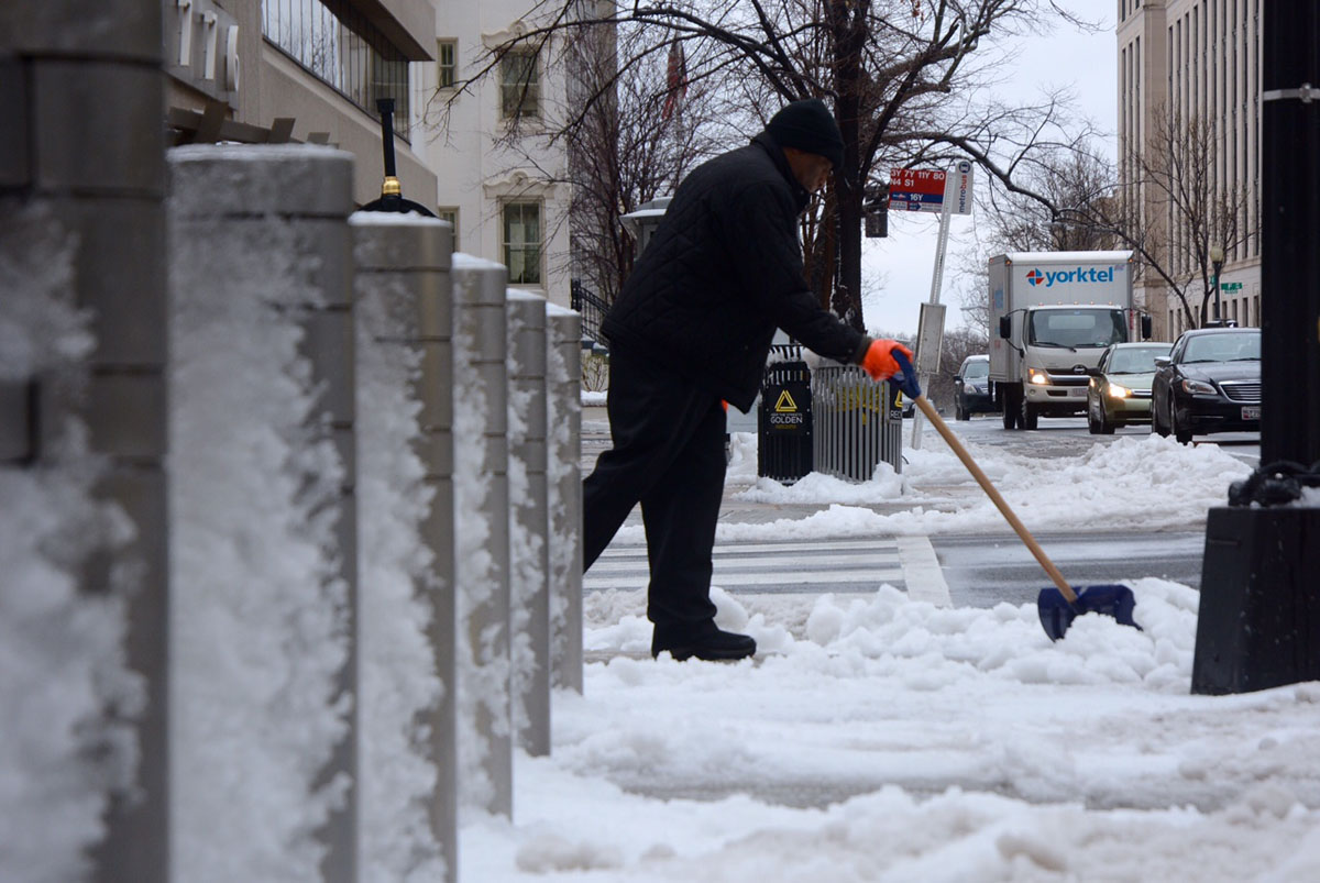 A man shovels a sidewalk on G Street in Northwest D.C. near the White House on March 14, 2017. A late-winter storm dumped snow, sleet and freezing rain over much of the D.C. region. (WTOP/Dave Dildine)