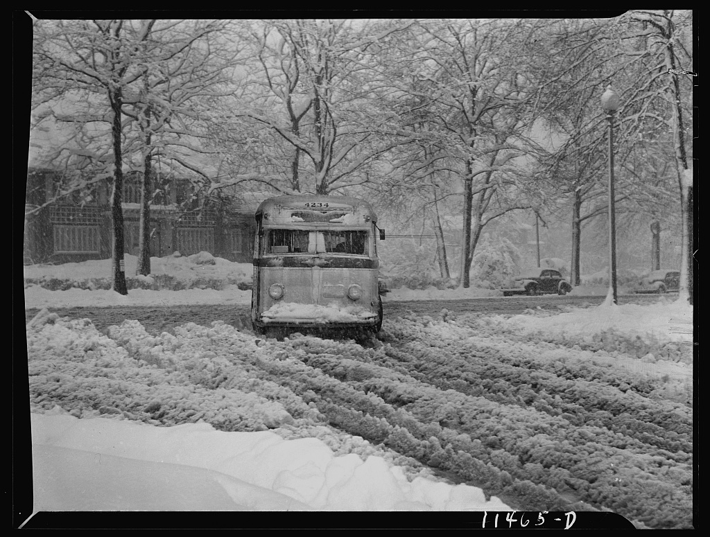 Washington, D.C. Bus going through the snow near Connecticut Avenue and Chevy Chase Circle.   Ferrell, John, photographer. Washington, D.C. Bus going through the snow near Connecticut Avenue and Chevy Chase Circle. Mar. Photograph. Retrieved from the Library of Congress, <https://www.loc.gov/item/fsa1998022910/PP/>.