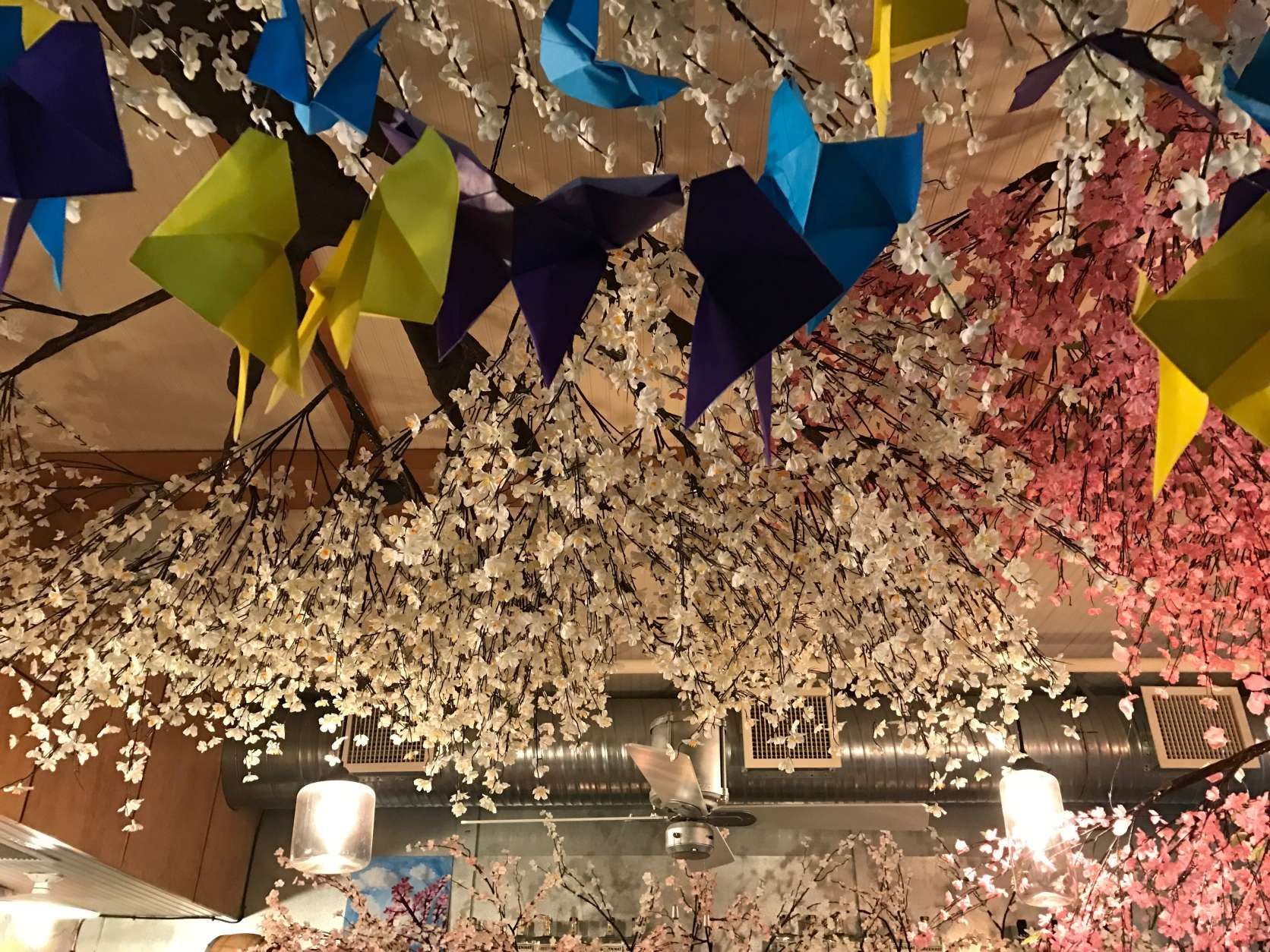 The blooms hanging above the Cherry Blossom pop up bar are also woven between the spirits behind the bar. (WTOP/Megan Cloherty)