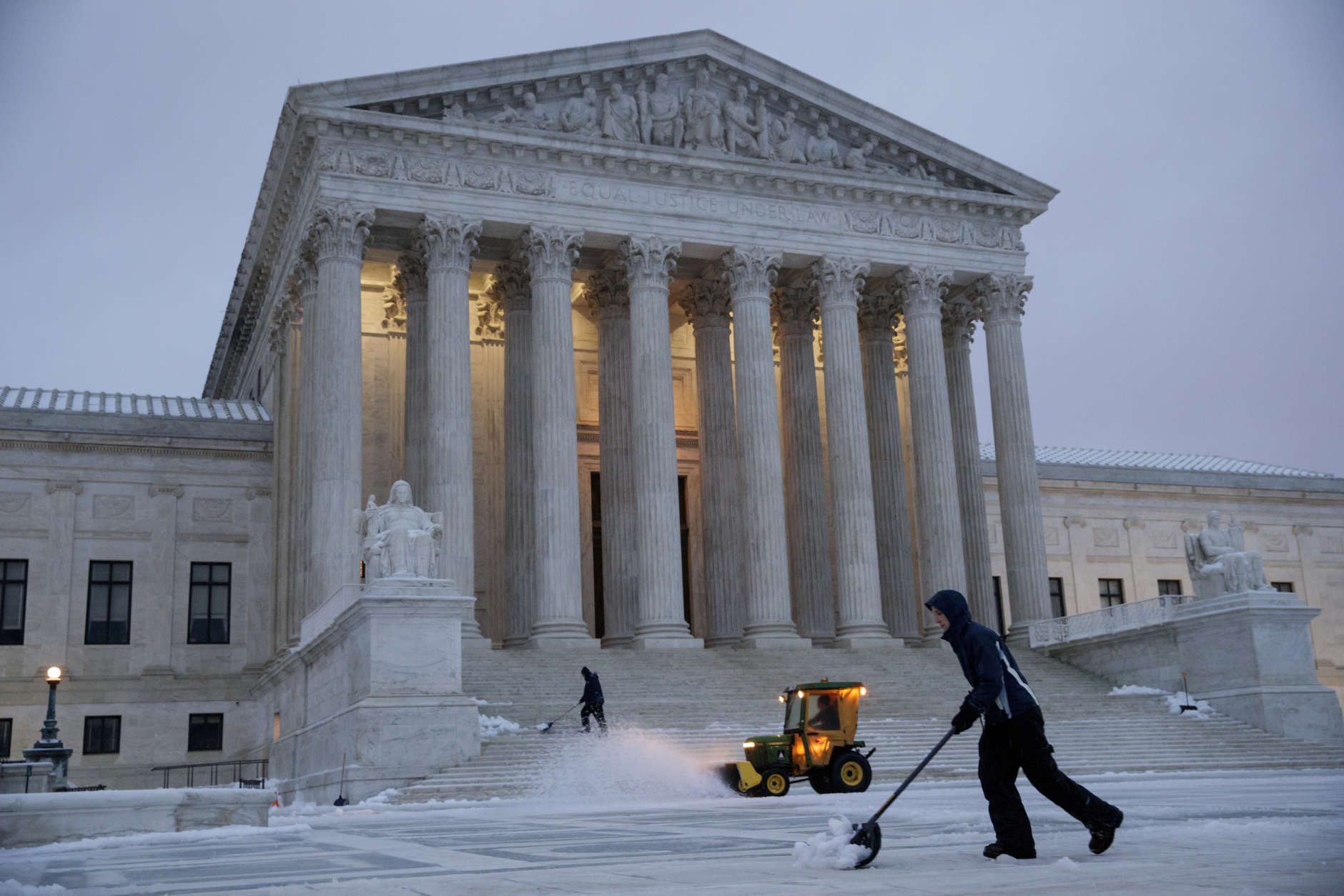Workmen clear snow in front of the Supreme Court on Capitol Hill in Washington, Tuesday, March, 14, 2017. A late-season storm is dumping a messy mix of snow, sleet and rain on the mid-Atlantic, complicating travel, knocking out power and closing schools and government offices around the region. (AP Photo/J. Scott Applewhite)