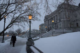 A man walks past the Library of Congress in the snow, on Capitol Hill in Washington, early Tuesday, March, 14, 2017. A late-season storm is dumping a messy mix of snow, sleet and rain on the mid-Atlantic, complicating travel, knocking out power and closing schools and government offices around the region.  (AP Photo/J. Scott Applewhite)